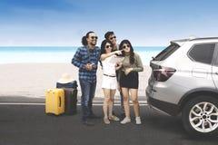 Junge Leute, die nahe dem Strand stehen Lizenzfreie Stockbilder