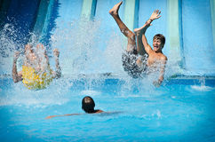Junge Leute, die Spaß auf Wasserrutschen im Aquapark haben Stockfotografie