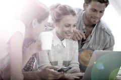 Junge Leute, die Spaß unter Verwendung des Laptops haben Stockfotos