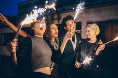 Junge Leute, die Sylvesterabend mit Feuerwerken genießen Stockbild