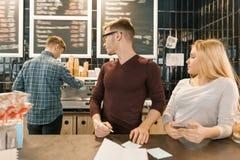 Junge Leute, die telefonisch in der Kaffeestube, im Mann und in der Frau nahe Barzähler, empfangender Auftrag, barista auf dem Hi stockfotografie