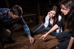 Junge Leute, die versuchen, eine Vexierfrage zu lösen, um eine Falle zu verlassen Lizenzfreie Stockbilder