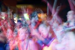 Junge Leute drängen Tanzen und das Zujubeln während einer Rockbandmusik-Konzertleistung an einem Festival