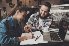 Junge Leute ergänzen Dokumente während in einem Café stockfoto