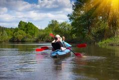 Junge Leute fahren auf einem Fluss in der schönen Natur Kayak Sonniger Tag des Sommers Stockfoto