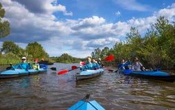 Junge Leute fahren auf einem Fluss in schönem Kayak Stockbild
