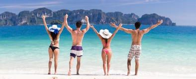 Junge Leute-Gruppe auf Strand-Sommer-Ferien, zwei Paare angehobene Handfreund-Küste stockbilder