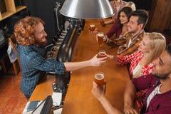 Junge Leute-Gruppe in der Bar, Kellner-Friends Sitting At-hölzerne Gegenkneipe, Getränk-Bier stockfoto