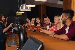 Junge Leute-Gruppe in der Bar, Kellner-Friends Sitting At-hölzerne Gegenkneipe, Getränk-Bier stockfotos