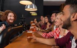 Junge Leute-Gruppe in der Bar, Kellner-Friends Sitting At-hölzerne Gegenkneipe, Getränk-Bier lizenzfreies stockbild