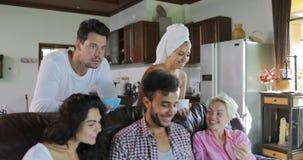 Junge Leute-Gruppen-Morgen Frühstücks-Sit On Coach In Modern-Studio-Wohnungs-Unterhaltungsgebrauchs-Laptop-Computer habend stock video footage
