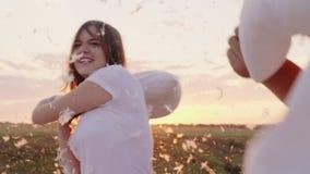 Junge Leute haben wütend Spaß Eine Frau schlägt ihr Kissen mit einem Freund, Federn fliegen Kampf gegen