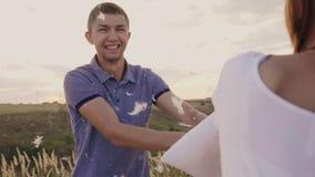Junge Leute haben wütend Spaß Eine Frau schlägt ihr Kissen mit einem Freund, Federn fliegen Kampf gegen stock video footage