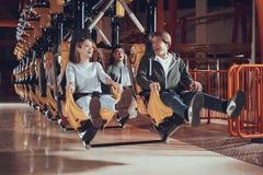 Junge Leute heben ihre Füße beim Sitzen auf dem Karussell an lizenzfreies stockfoto
