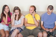 Junge Leute an ihren Telefonen Lizenzfreies Stockbild