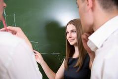 Junge Leute lösen ein Problem auf einem Vorstand Lizenzfreie Stockfotografie