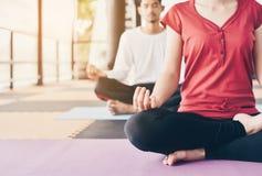 Junge Leute meditieren auf bunten Reifen für gute Gesundheit stockbilder