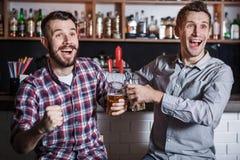 Junge Leute mit aufpassendem Fußball des Bieres in einer Bar Lizenzfreie Stockfotos