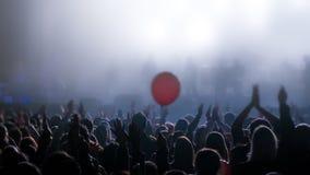 Junge Leute mit den Händen in der Luft während des Rockkonzerts silhouettiert gegen helle Lichter lizenzfreies stockfoto