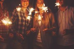 Junge Leute mit den Wunderkerzen, die Spaß auf Partei im Freien haben Lizenzfreie Stockfotos