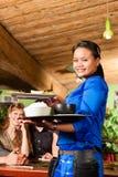 Junge Leute mit der Kellnerin, die im thailändischen Restaurant isst lizenzfreie stockfotos