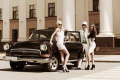 Junge Leute mit einem klassischen Auto Stockbild