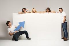 Junge Leute mit einem leeren Vorstand lizenzfreies stockfoto