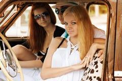 Junge Leute mit einem Retro- Auto Stockfoto