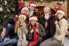 Junge Leute nahe dem Weihnachtsbaum Stockbilder
