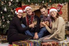 Junge Leute nahe dem Weihnachtsbaum Stockfoto