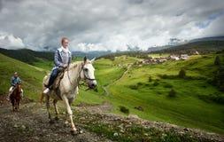 Junge Leute reiten Pferde in den Bergen in der Provinz von Tus lizenzfreies stockfoto