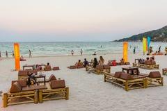 Junge Leute sitzen auf Teppichen an den niedrigen Tischen auf einem tropischen Strand Lizenzfreies Stockfoto