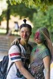 Junge Leute sprechen während des Festivals der Farbe in einem Stadtpark Lizenzfreie Stockfotos