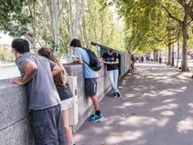 Junge Leute starren über Steinwand zur Seine in Paris an Stockfotografie