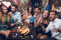 Junge Leute stehen in einem modischen Nachtklub still Ein Kerl in einem weißen Hemd und ein Mädchen in einem schwarzen Kleid sing stockfotografie