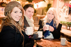 Junge Leute-trinkender Locher am Weihnachtsmarkt Lizenzfreie Stockfotos