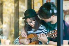 Junge Liebespaare, die zusammen Gitarre im Café spielen Lizenzfreie Stockfotos