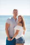 Junge liebevolle Paare auf dem Strand nahe dem Meer Lizenzfreies Stockfoto