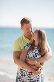 Junge liebevolle Paare auf dem Strand nahe dem Meer Lizenzfreie Stockfotografie