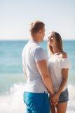 Junge liebevolle Paare auf dem Strand nahe dem Meer Stockfotografie