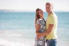 Junge liebevolle Paare auf dem Strand nahe dem Meer Stockbilder