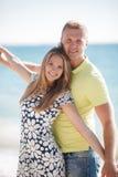 Junge liebevolle Paare auf dem Strand nahe dem Meer Lizenzfreie Stockfotos