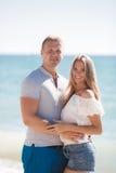 Junge liebevolle Paare auf dem Strand nahe dem Meer Stockbild