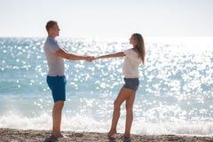 Junge liebevolle Paare auf dem Strand nahe dem Meer Lizenzfreie Stockbilder