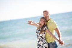 Junge liebevolle Paare auf dem Strand nahe dem Meer Stockfoto