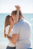 Junge liebevolle Paare auf dem Strand nahe dem Meer Lizenzfreies Stockbild