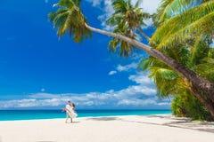 Junge liebevolle Paare auf tropischem Strand mit Palmen Stockfotografie