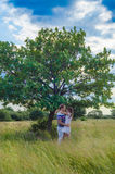 Junge liebevolle Paare, die auf dem Gebiet nahe einem tr sich umfassen Stockfoto