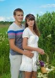 Junge liebevolle Paare, die auf dem Gebiet sich umfassen stockfoto