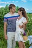 Junge liebevolle Paare, die auf dem Gebiet umfassen lizenzfreie stockfotos